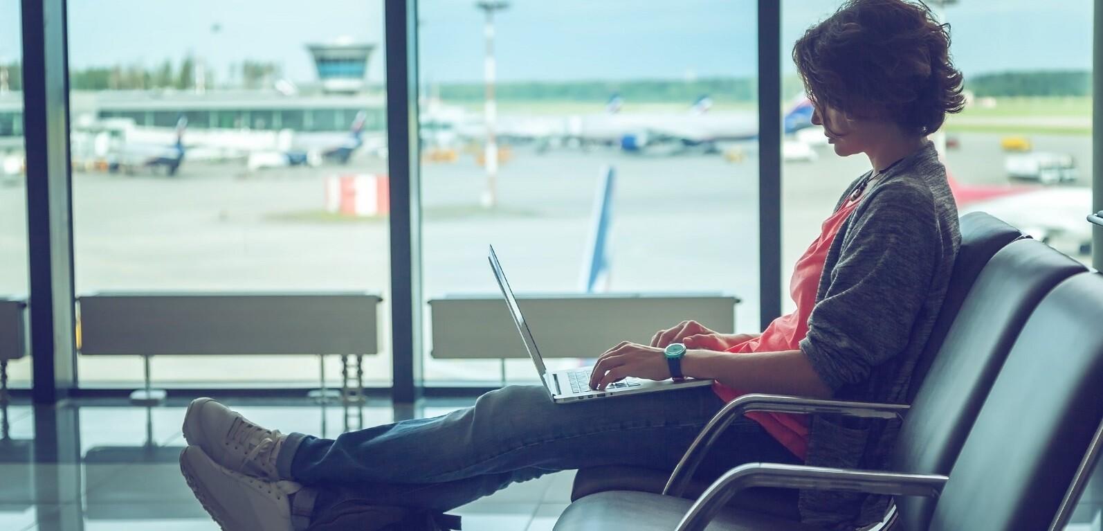 nômade digital: uma mulher de cabelo curto em um aeroporto com laptop no colo.