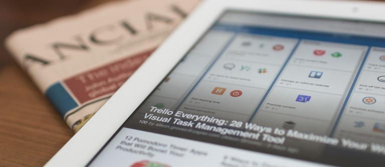 como usar o trello - tablet que mostra o trello aberto sobre um jornal