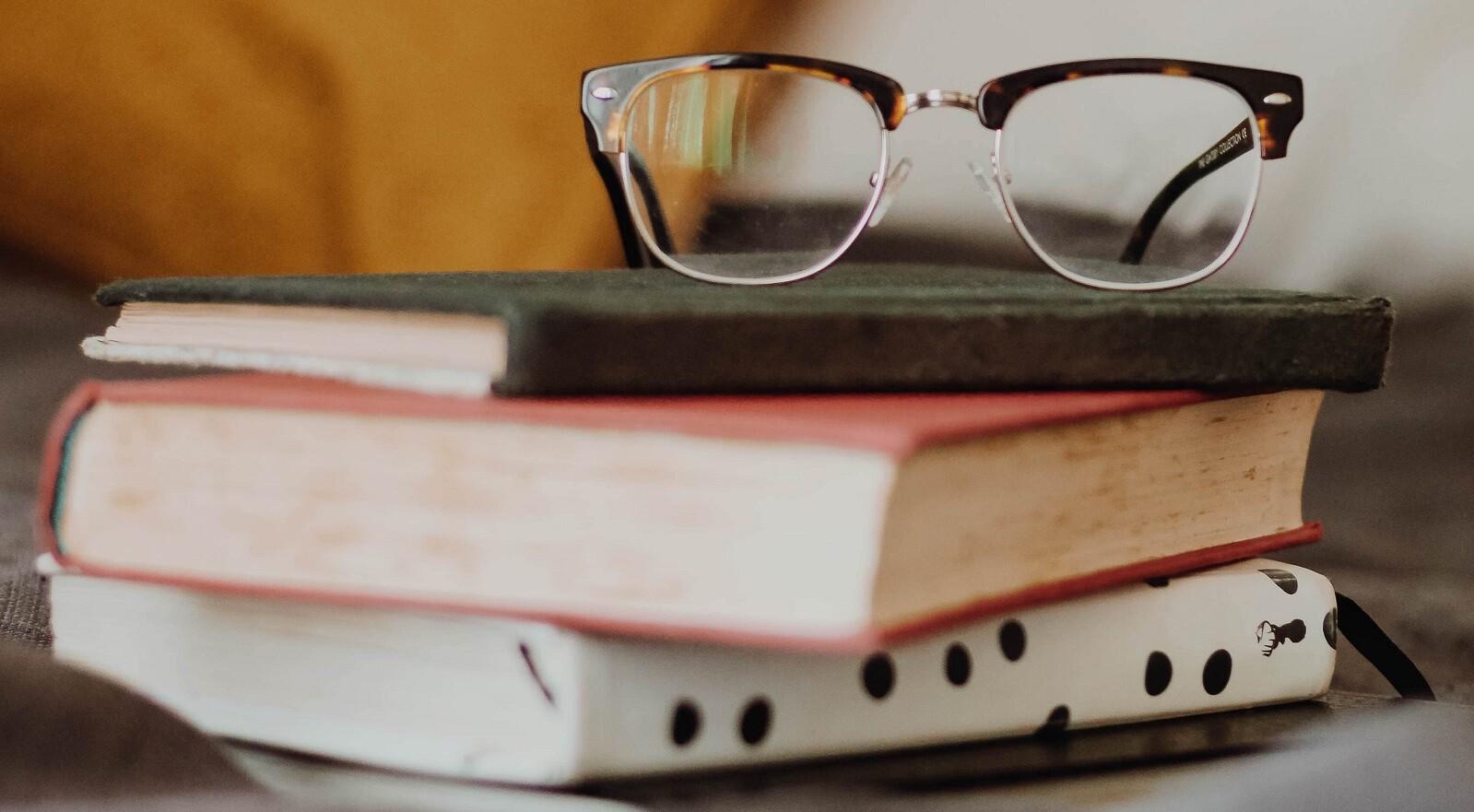 óculos apoiado em uma pilha de livros