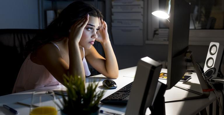 rotina do home office: mulher no home, no período da noite, demonstrando preocupação