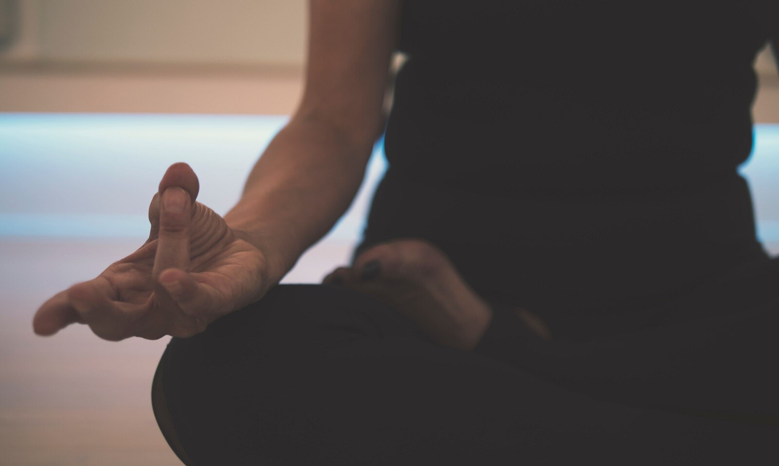 meditação e trabalho - imagem de mulher praticando meditação, sentada no chão