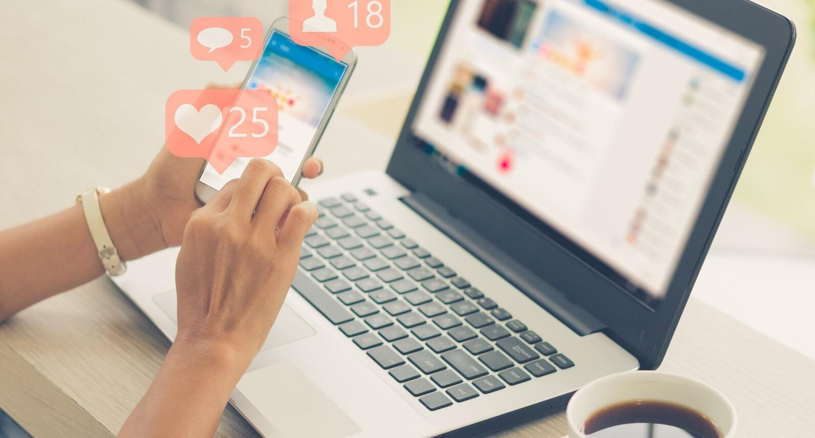 social media freelancer - imagem de mao feminina segurando um smartphone em frente a um notebook aberto