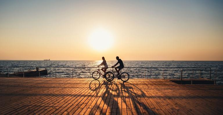 lifestyle design - perfil de duas pessoas andando de bicicleta, em frente ao mar, com um por do sol