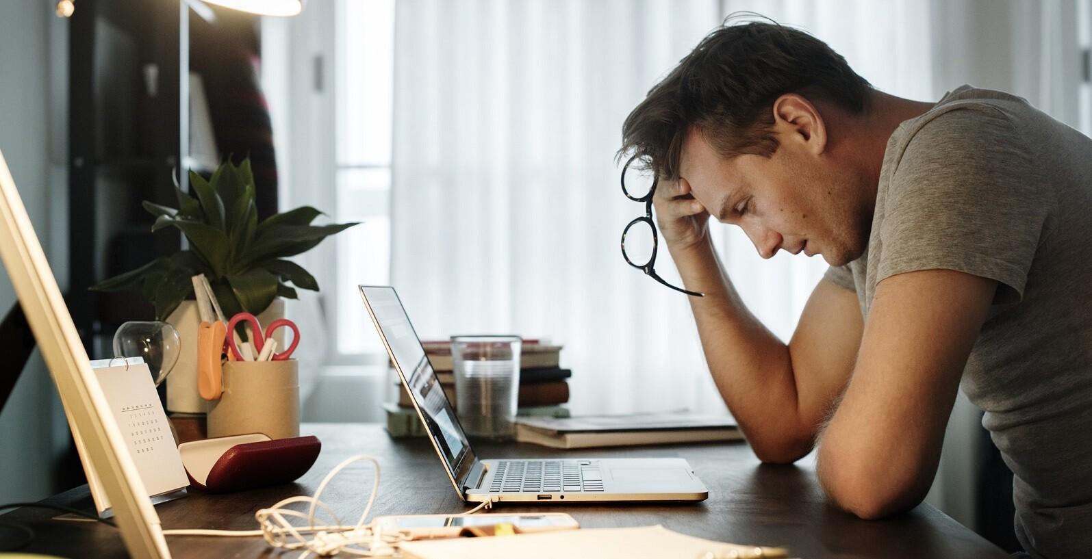 trabalho freelance - homem com a cabeça apoiada na mão, olhando pensativo para o computador