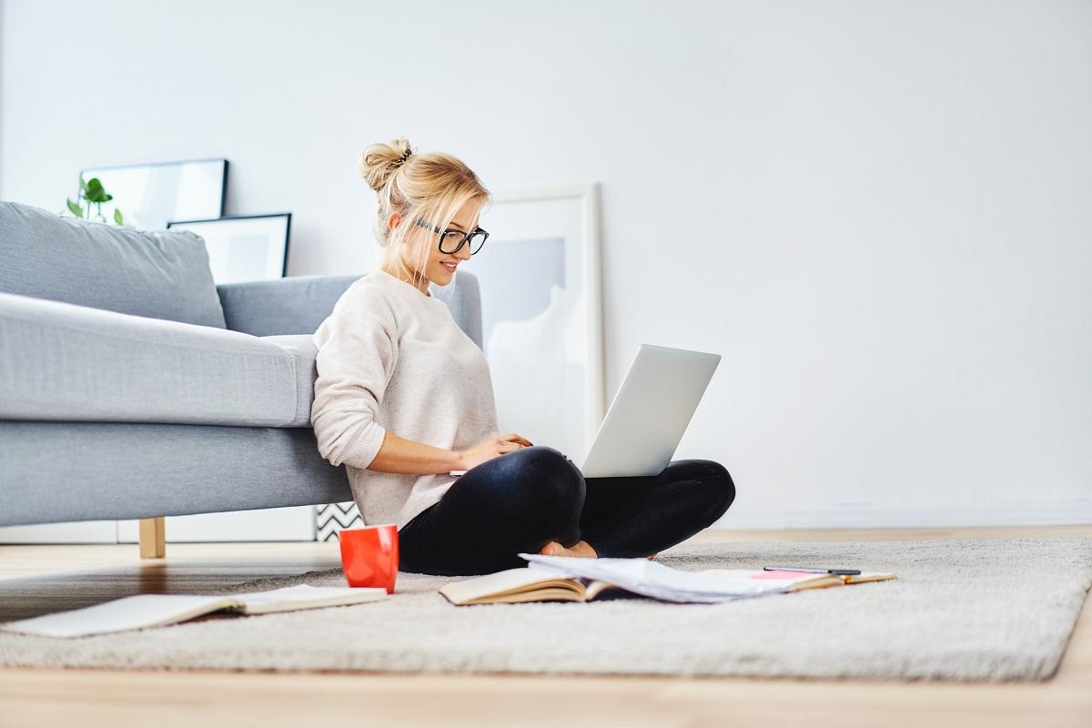 jornalista frelancer - a foto mostra uma moça loira e jovem, sentada no chão e encostada em um sofá, trabalhando com um notebook. Ela sorri.