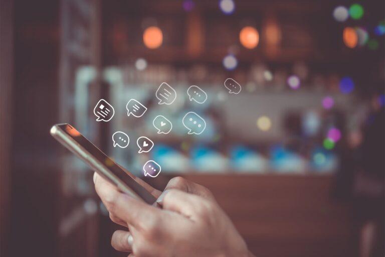 acessibilidade nas redes sociais - a imagem mostra as mãos de uma mulher branca segurando um telefone celular. A partir do telefone, saem ilustrações que remetem aos ícones das redes sociais.